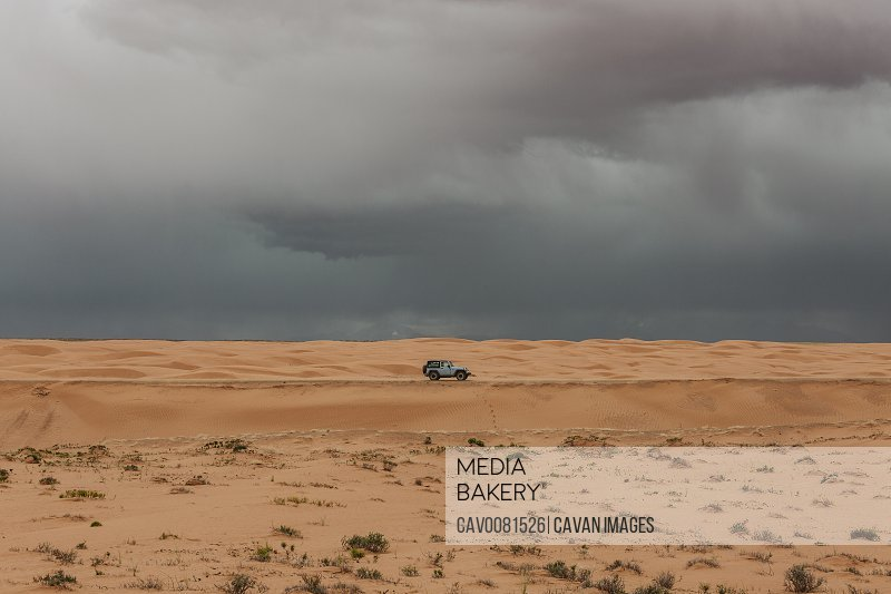 lone car under stormy rain clouds during a microburst in the desert