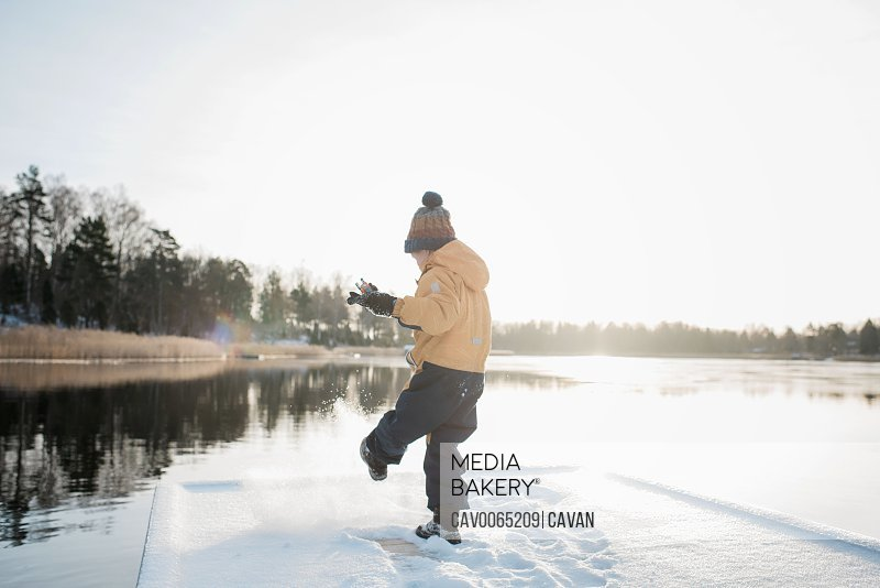 young boy playing in the snow at sunset by the Baltic sea in Sweden