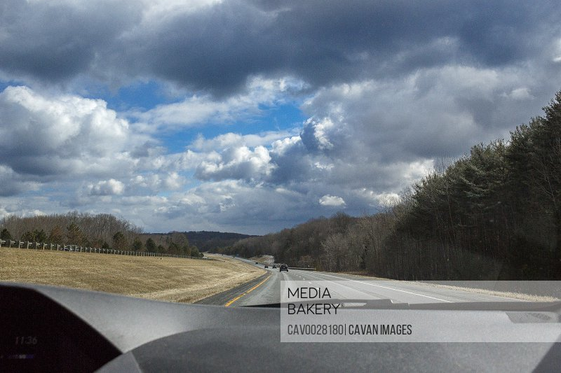 view out a windshield of a highway and cloud-filled sky above dash