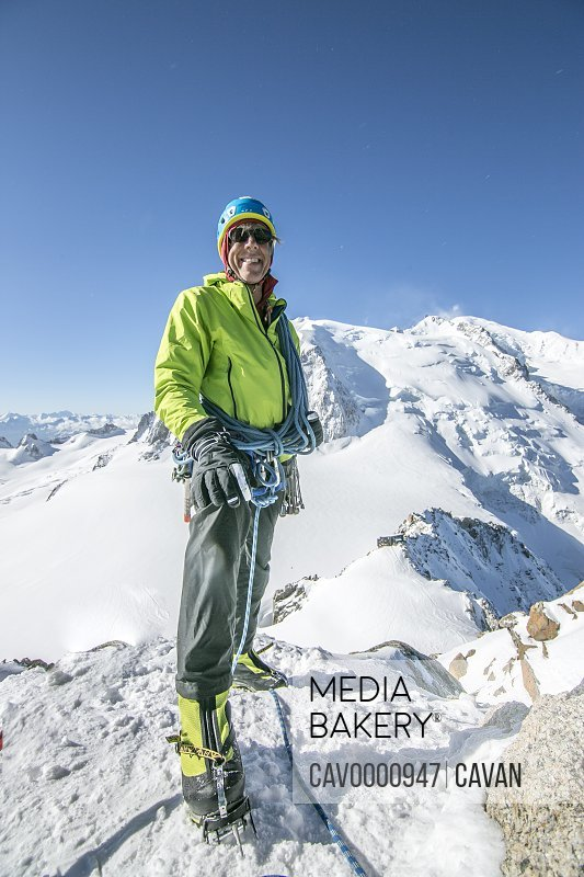 A smiling alpinist in his fifties stands tall on a snow promontory