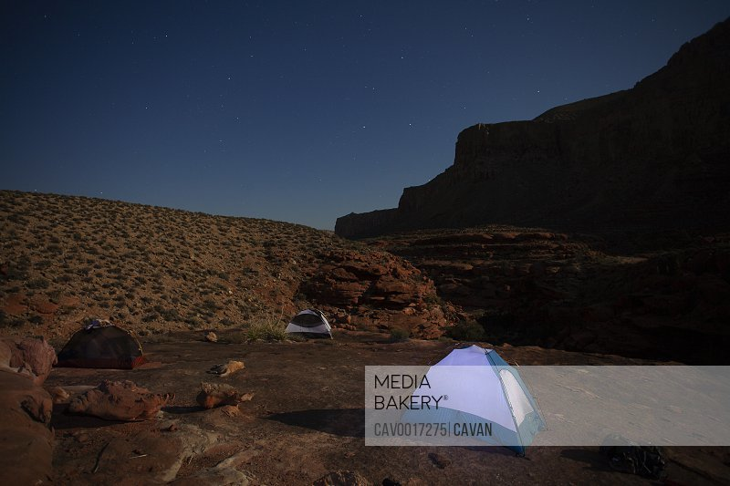 Tents illuminated by moonlight in a rugged desert environment at night