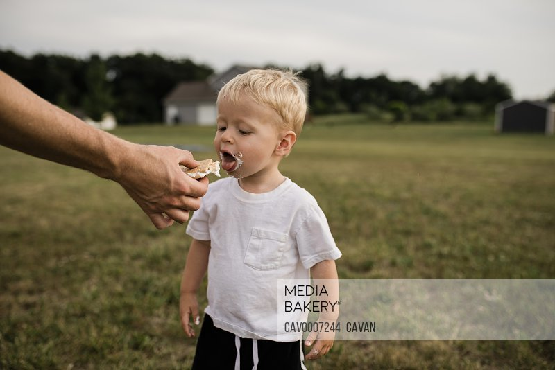 Toddler boy opens mouth to eat s'more from dad's hand in backyard