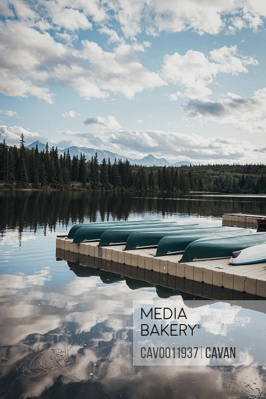Line of canoes on a dock on Pyramid Lake in Jasper, Alberta.