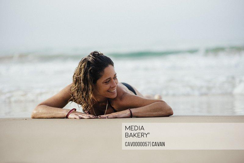 Woman with bikini smiling and sunbathing on the beach.
