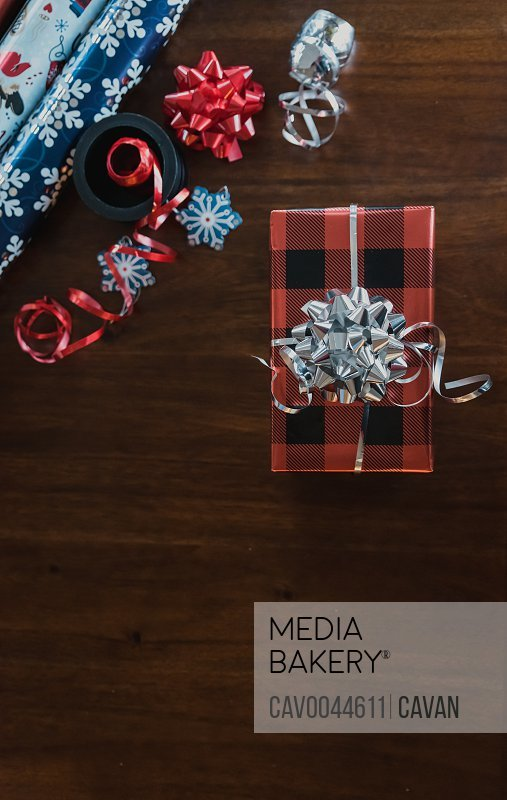Close up of wrapped present and gift wrap supplies on a wooden table.