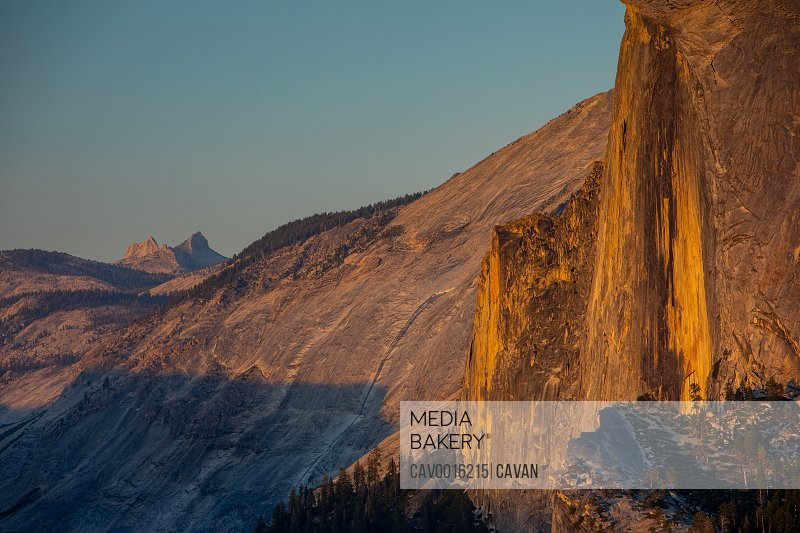 The vertical face of Half Dome at sunset in Yosemite with Echo Peaks