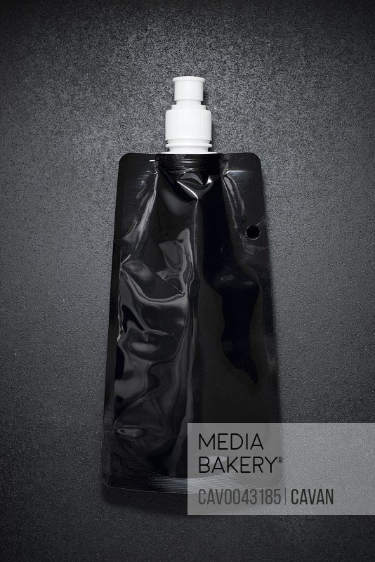 Flexible plastic bottle on a black table.