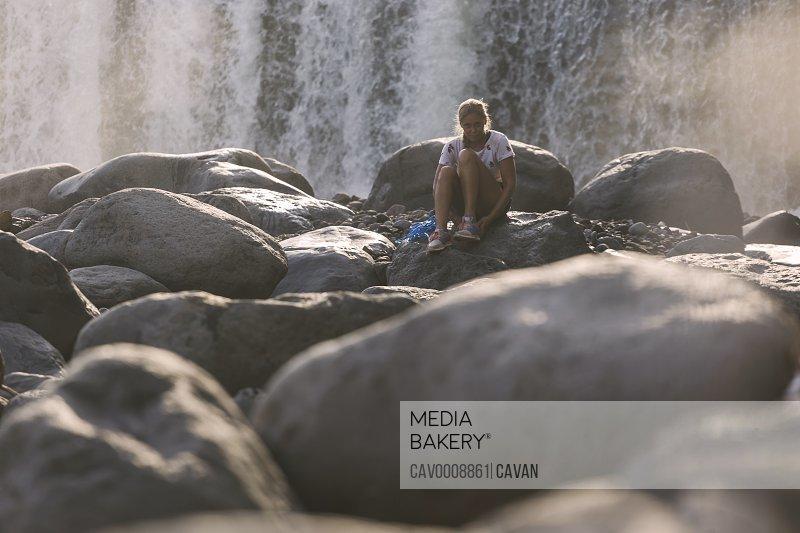 Young woman near waterfall