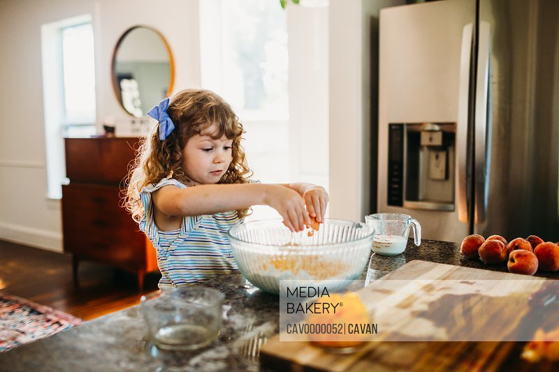 Young girl cracking egg into bowl of peach muffin batter