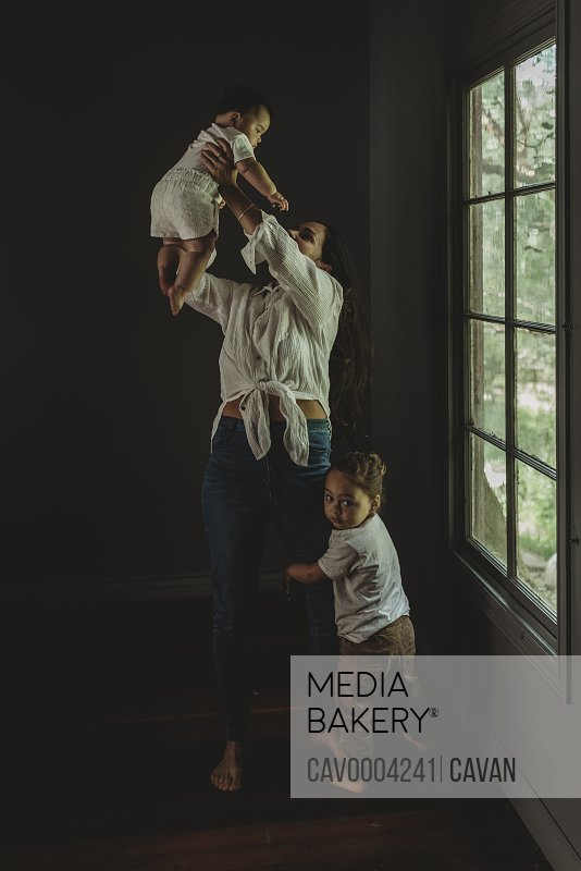 Young mother lifting baby daughter in the air while son hugs her