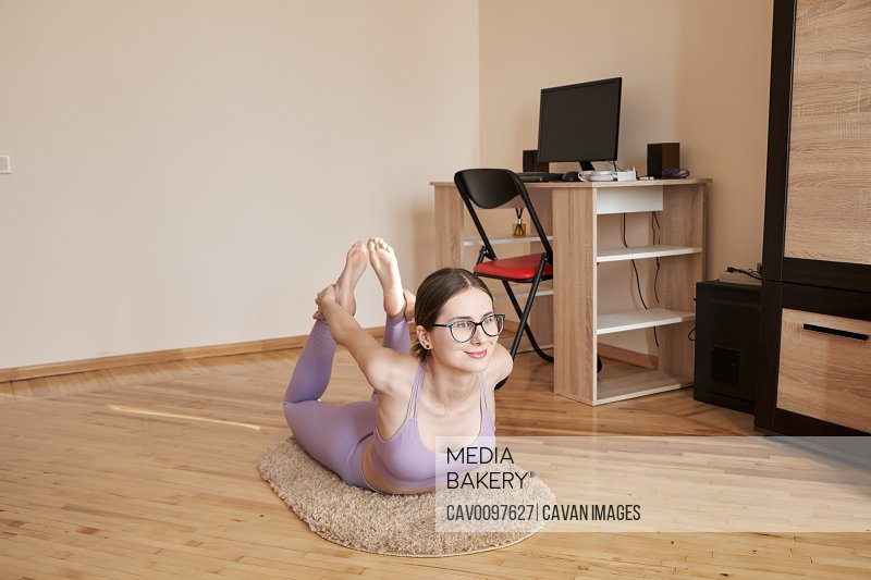 young woman in glasses is charging at home near workplace