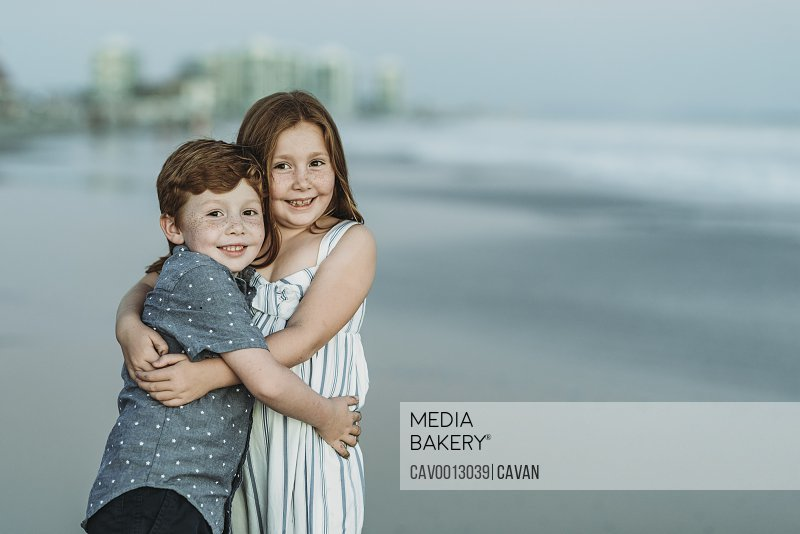 Portrait of brother and sister hugging at the beach at dusk