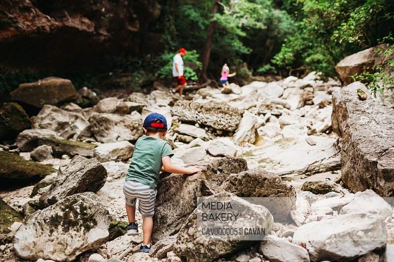 Young boy climbing rocks to catch up with dad and sister while hiking