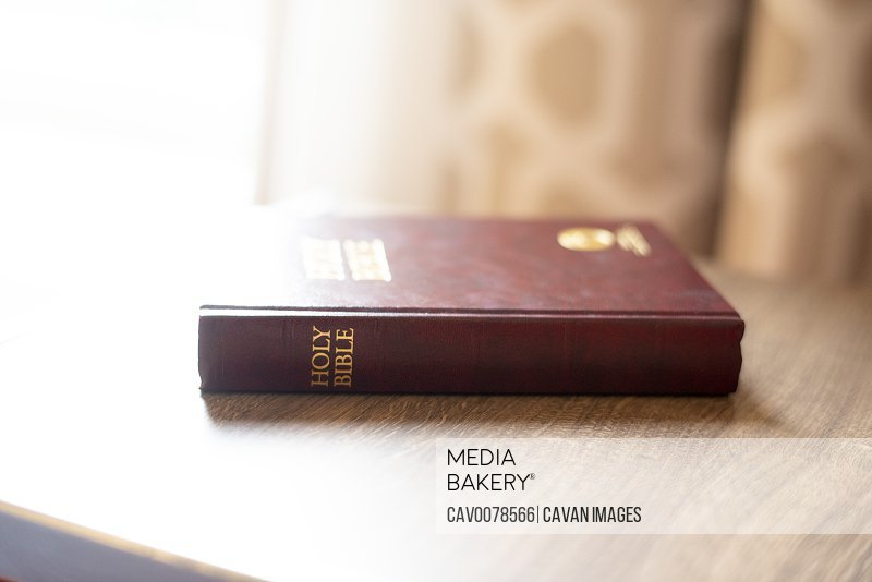 Back lit Holy Bible on side table in motel room