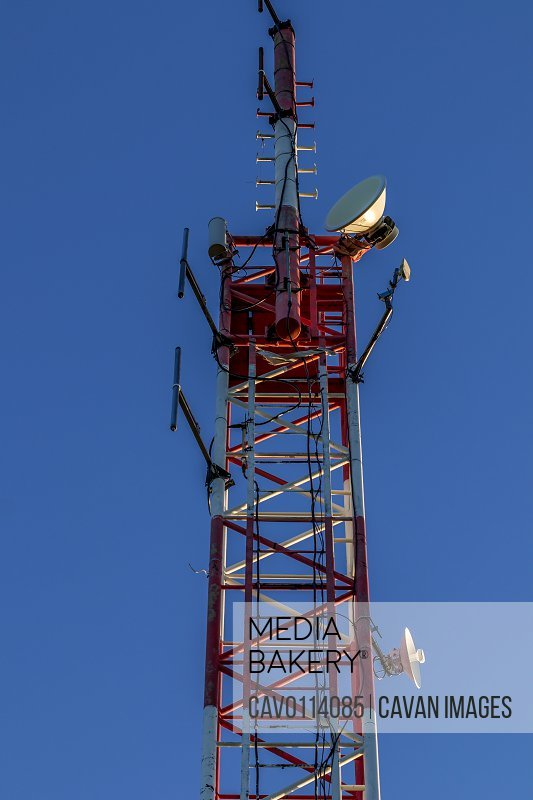 Closeup of a broadcast tower full of devices with a blue sky in the background.