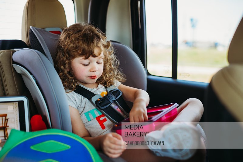 Young girl sitting in a car seat and eating lunch on a road trip