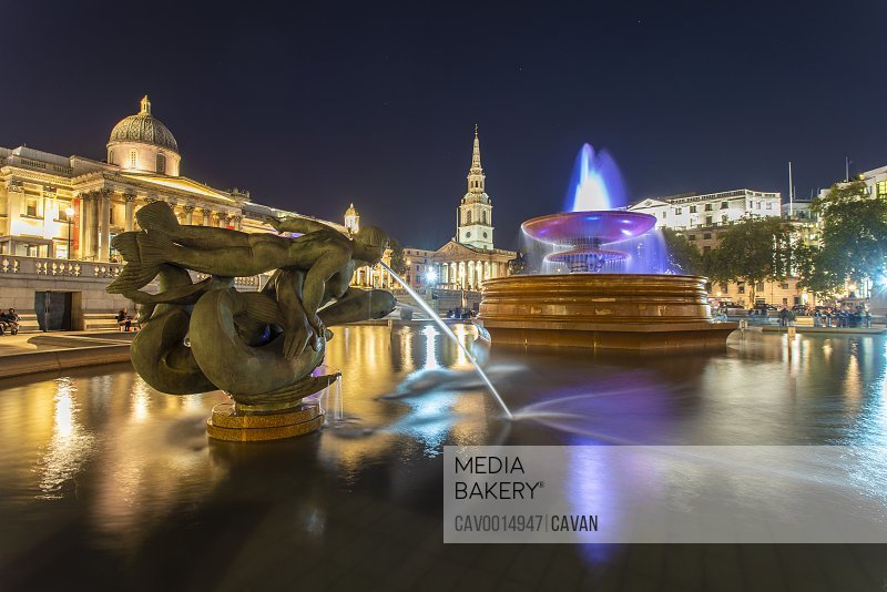 Trafalgar square at night with the national gallery in the background