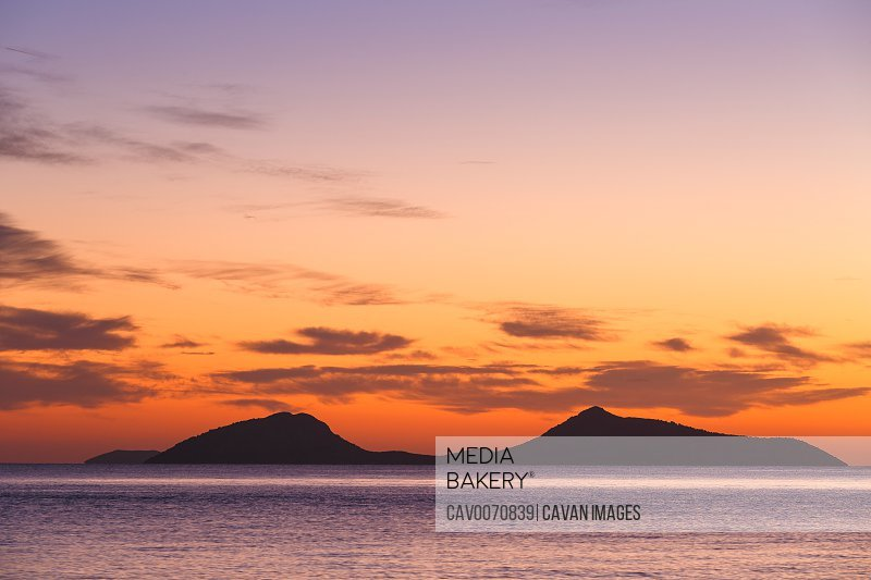 View of Trikeri island against colorful morning sky from Spetses.