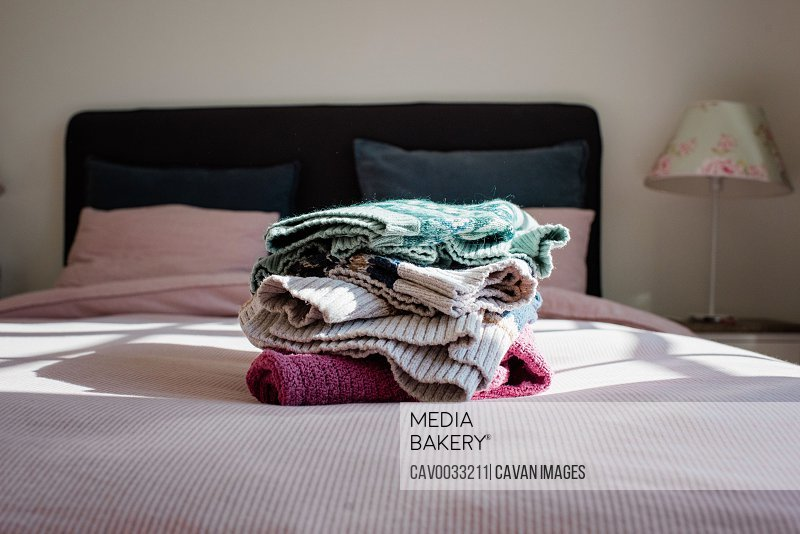 neatly folded winter fair isle sweaters on a bed in a bedroom at home
