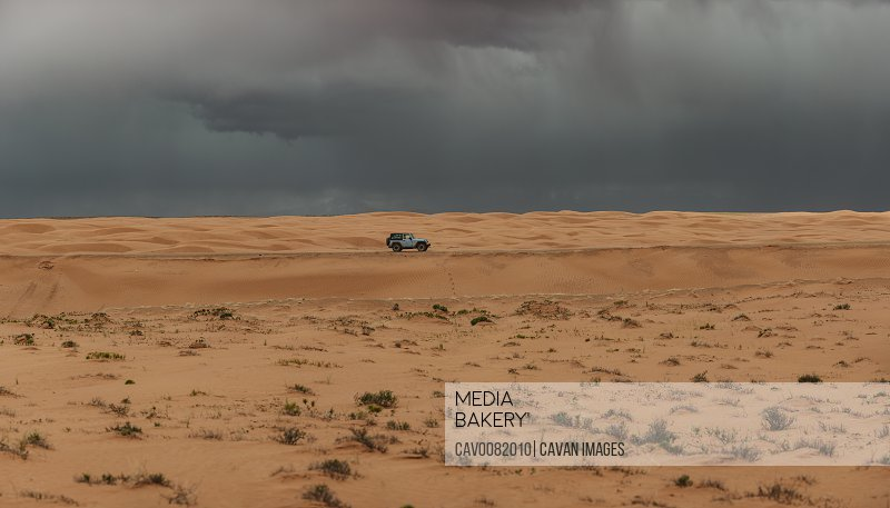 Jeep drives through the sand dunes of Utah under stormy skies