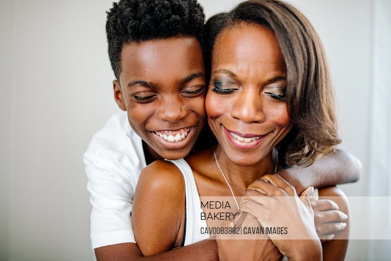 Happy African-American boy hugging mom with closed eyes