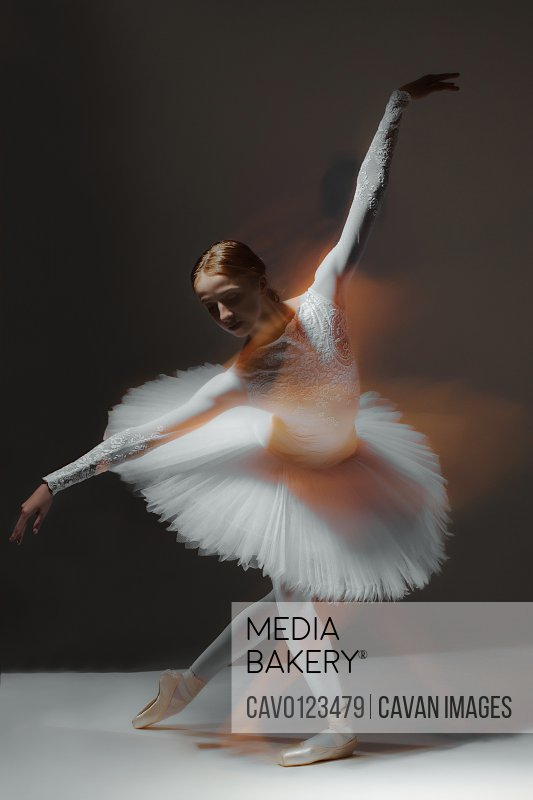 ballerina in white ballet dress dancing in dark class, motion blur