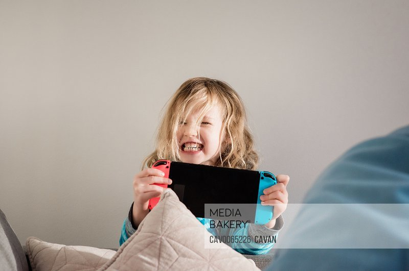 young girl pulling faces whilst playing Nintendo switch at home