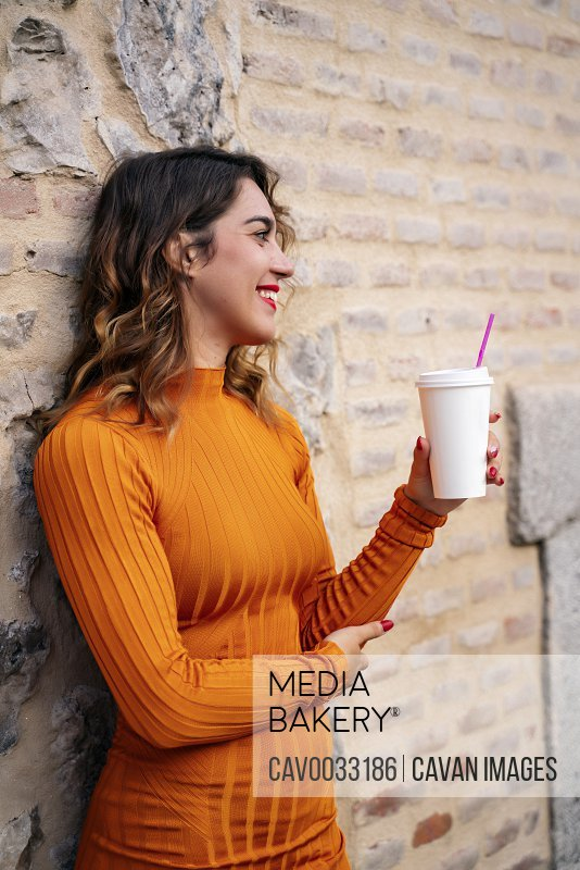 attractive young woman drinking coffee in the street