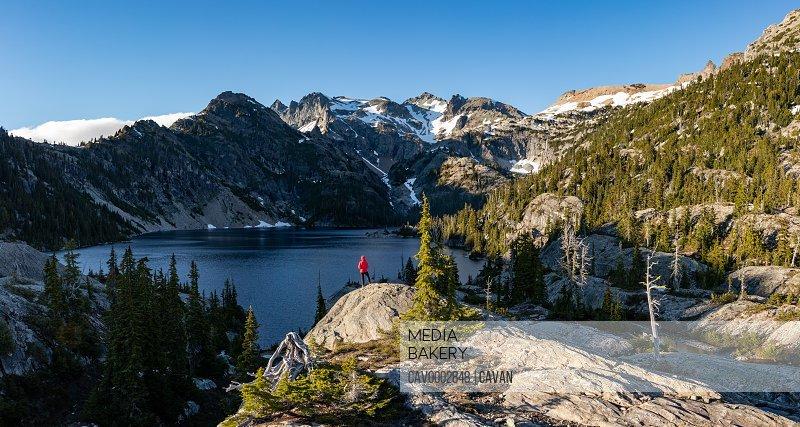 Hiker girl gazes at beautiful lake panorama in Alpine Lakes Wilderness