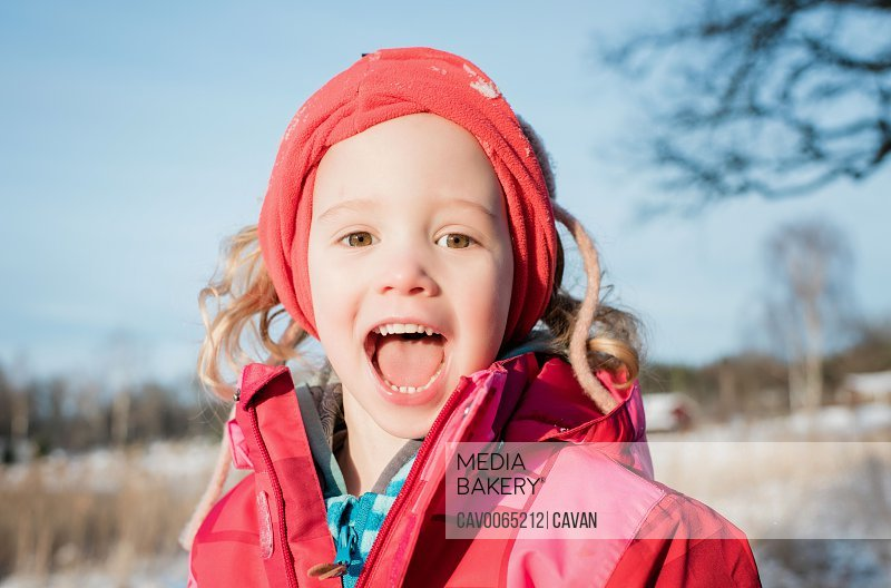 portrait of young girl laughing whilst playing outside in winter