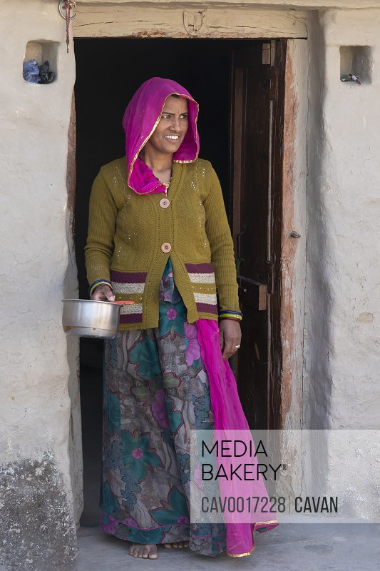 A woman in traditional clothes in doorway holds a pot in India. <br><br><span style='color: red'>Editorial Use Only.</span><br><br>