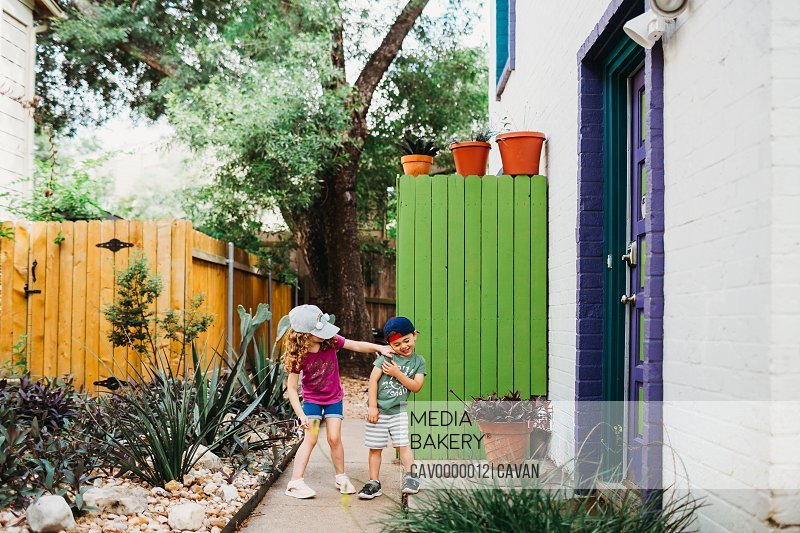 Young girl tickling brother outside a colorful town home