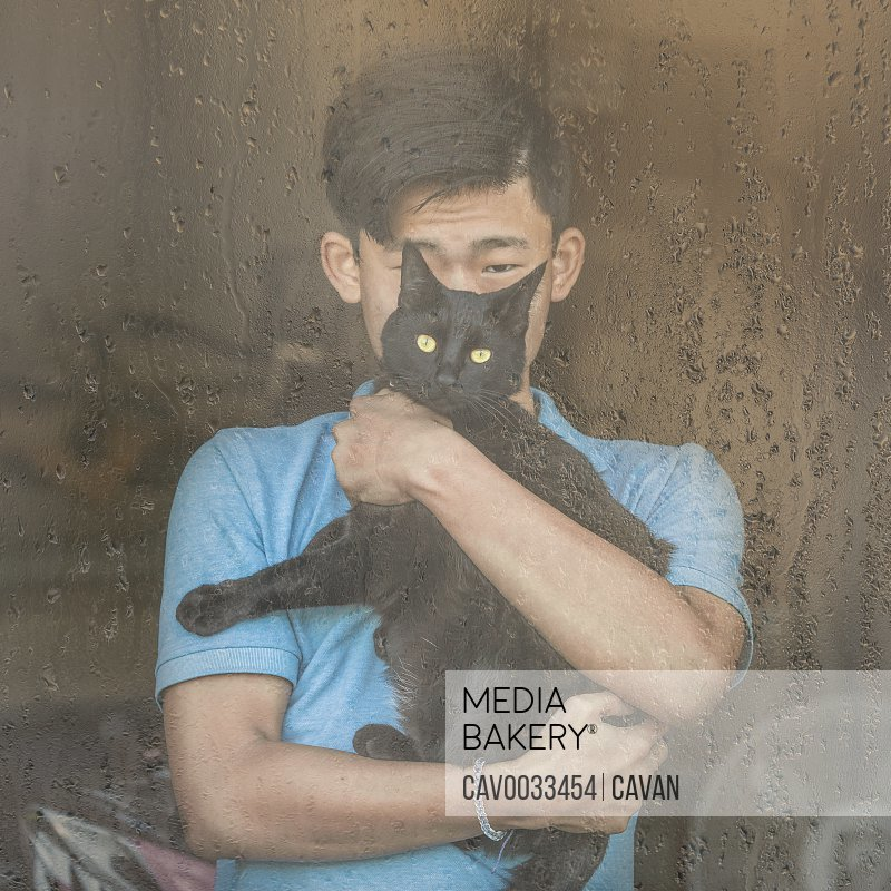 Asian Chinese boy and black cat look out rain streaked window