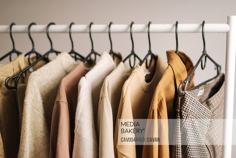 Rack filled with clothing on white background