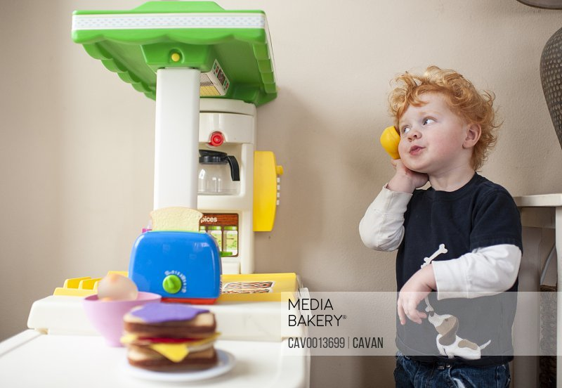Toddler boy answering phone in his play kitchen with cute expression