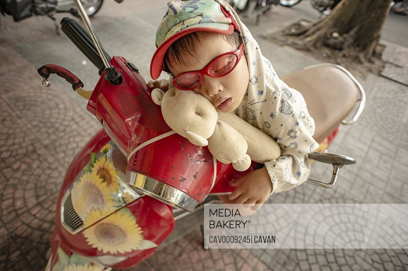 Cute boy sleeping in the streets on a red scooter <br><br><span style='color: red'>Editorial Use Only.</span><br><br>