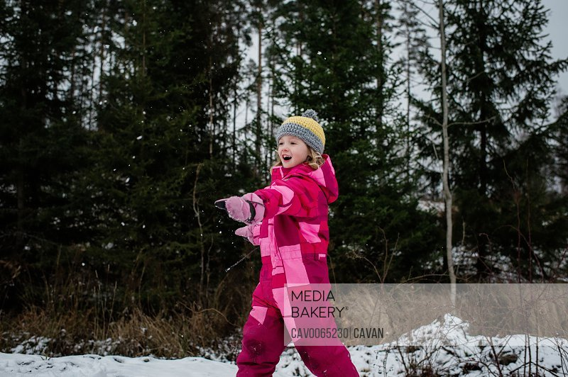 girl playing in the snow laughing throwing a snowball