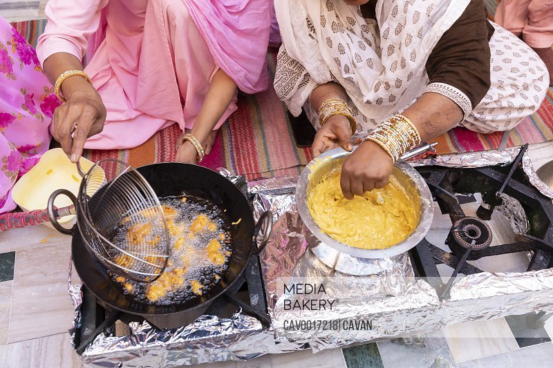 Women's hands make pakoras (Indian chickpea-battered fritters). <br><br><span style='color: red'>Editorial Use Only.</span><br><br>