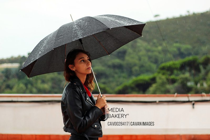 Young woman with a leather jacket holds open black umbrella.