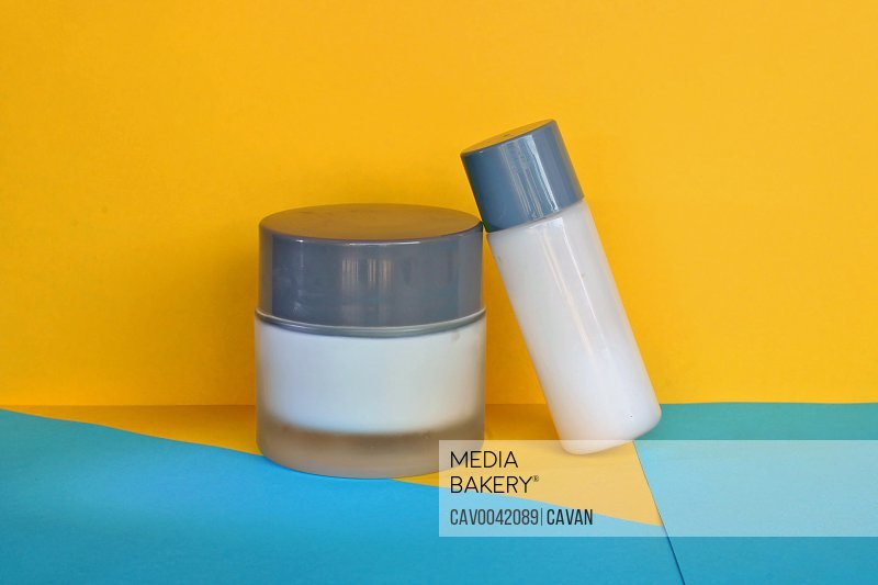 Two bottles of natural cream on a blue and yellow background.