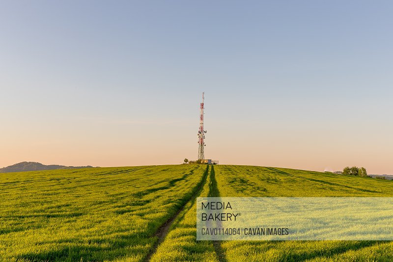 View of a broadcasting tower lying on a hill in the middle of a landscape in a field on a hill.