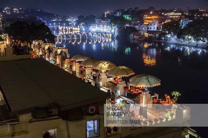 Night view of rooftop restaurant with umbrellas overlooking a river.