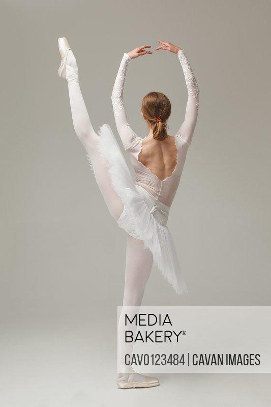 professional ballet dancer doing ballet move developpe, studio shot
