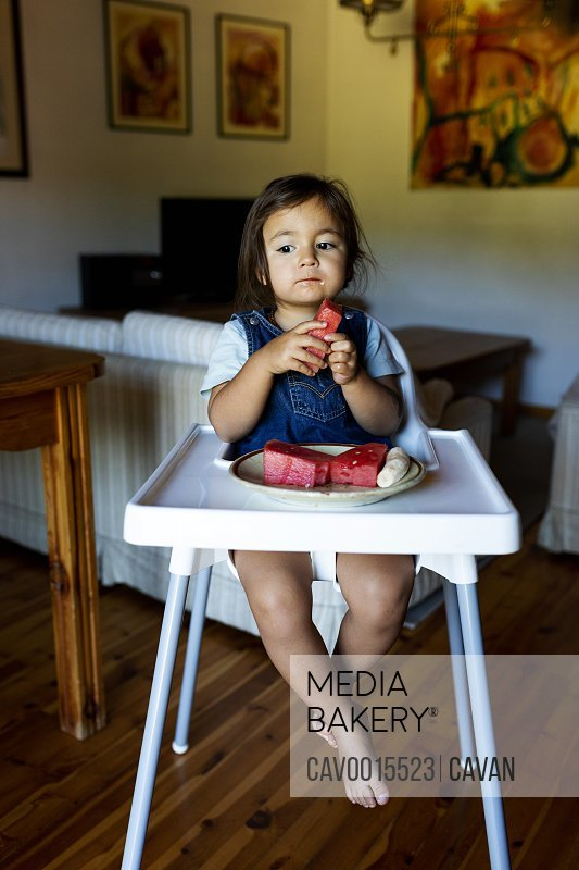Smiling toddler in high chair eating watermelon