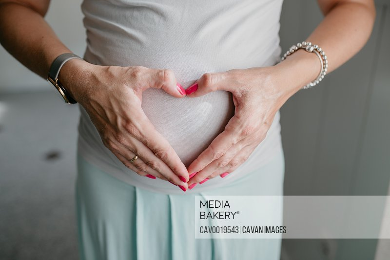 Pregnant woman makes a heart with her hands on her belly