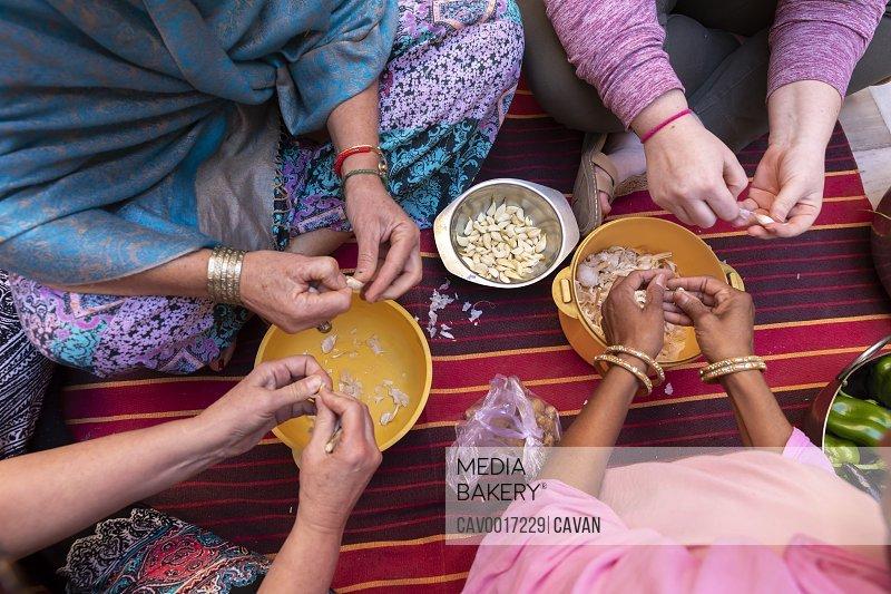 A detail shot of diverse women's hands preparing garlic..