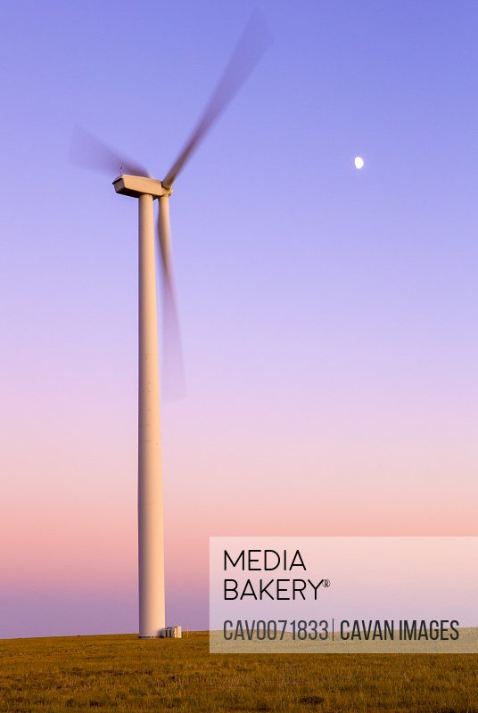 Wind Turbine in motion against purple sky with moon