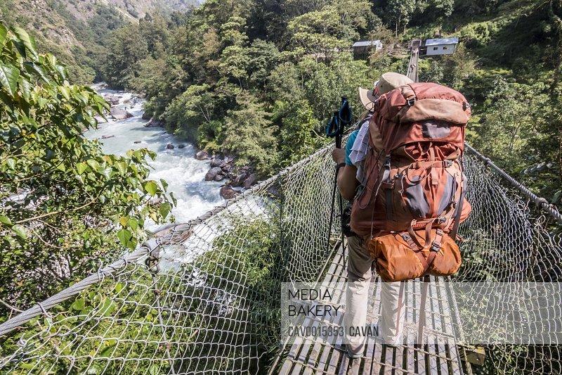 Woman with big backpack crosses suspension bridge in Nepal
