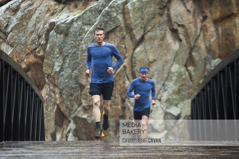 Men trail run in rain across creek bridge in Boulder Canyon, Colorado
