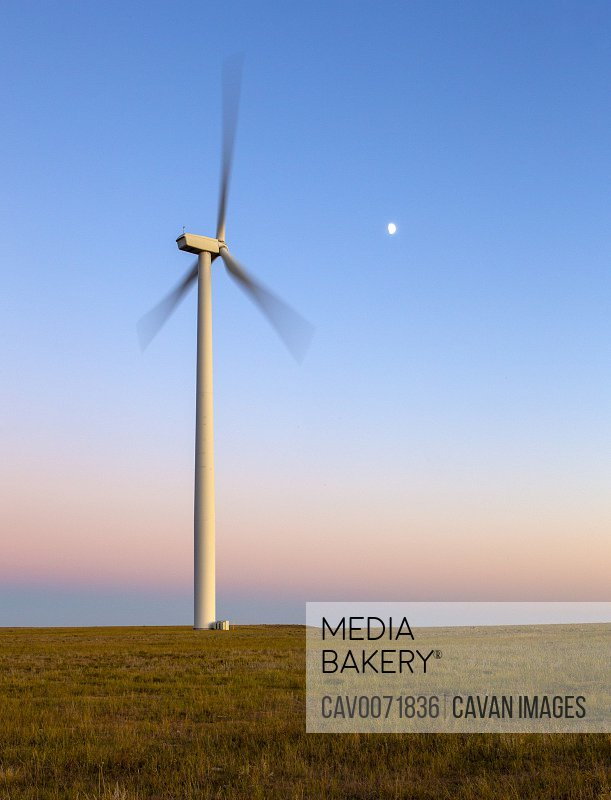 Wind Turbine in motion against blue sky with moon